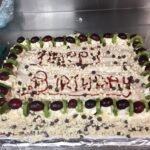 Birthday cake decorated with fruits, chocolates and grapes
